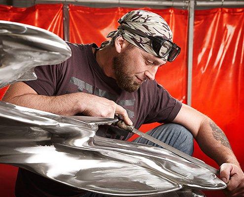 Das BIV Kampanenbild 2 zeigt einen Metallbildner beim feilen einer Skulptur