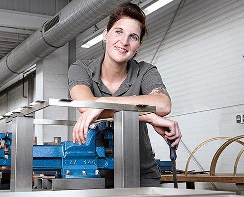 Das BIV Kampanenbild 5 zeigt eine Metallbildnerin auf einen Schraubstock gestützt